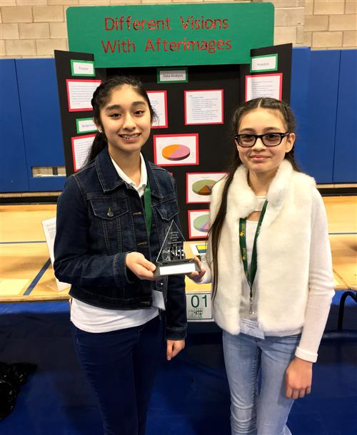 2 middle school students with project and trophy