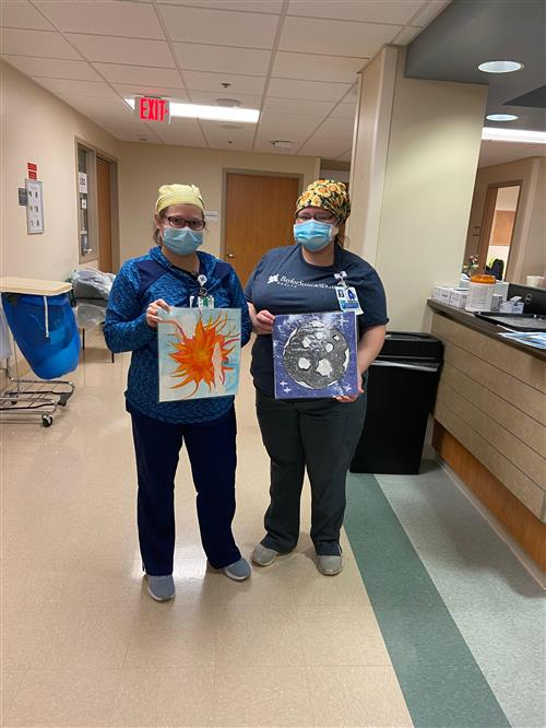 Nurses from Hillcrest holding sun and moon paintings