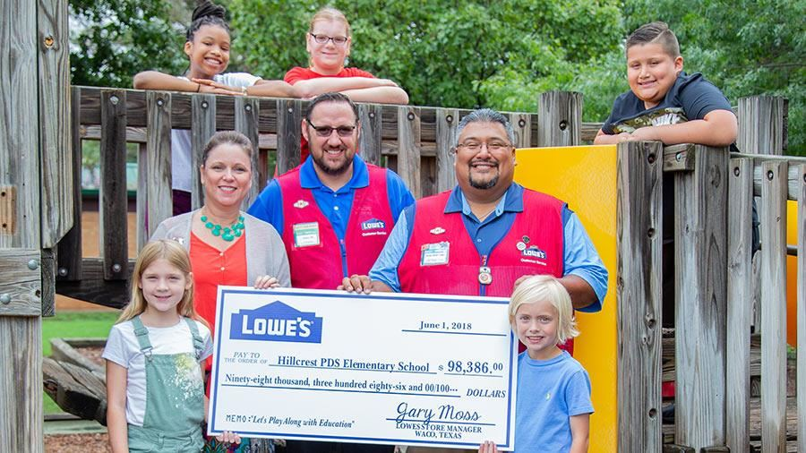 Waco Lowe's store managers present an oversized check in the amount of $98,386 to Hillcrest PDS to f