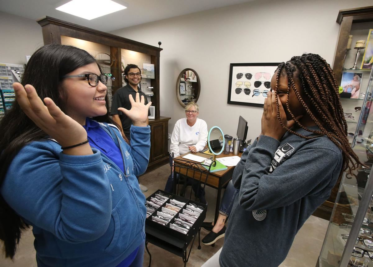 ISMS student Deanna Mollett (right) reacts as classmate Ofelia Franco tries on frames at Waco Vision Source